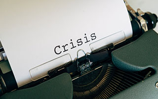 the word crisis on a white sheet of paper typed on a typewriter