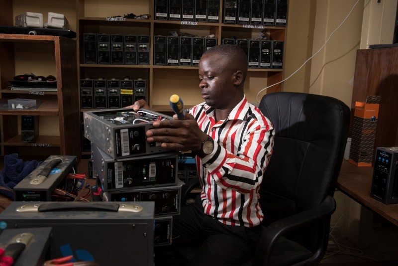BBOXX repair technician, Charles, refurbs a control box in the workshop at the BBOXX distribution centre. Kisumu, Kenya