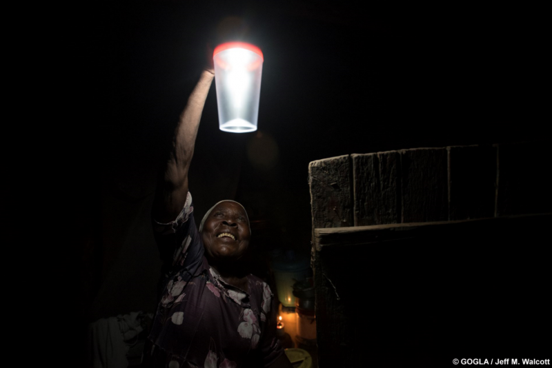 a woman hanging up a solar lamp GOGLA
