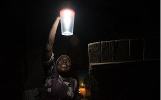 a woman hanging up a portable solar lantern