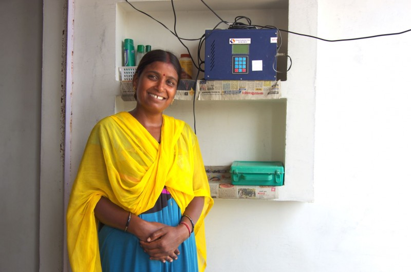 An Indian woman standing in front of a Simpa Networks Solar Home System