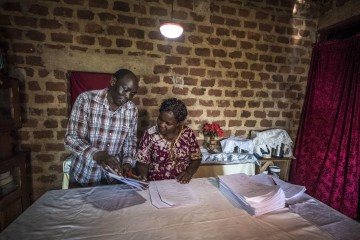A woman and a man standing in shop lightened by a solar light
